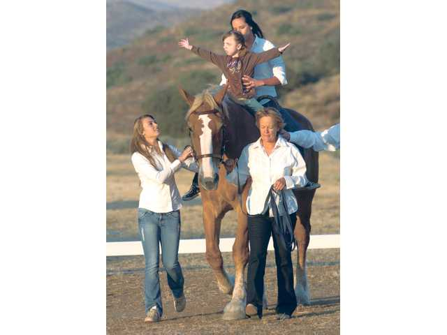Cassidy Rogers, 7, displays her therapeutic riding skills as Jolie Stroh, left, and Carousel Ranch founder Becky Graham lead Callie in front of the crowd for the Heart of the West fundraiser at Agua Dulce Airport on Aug. 28.