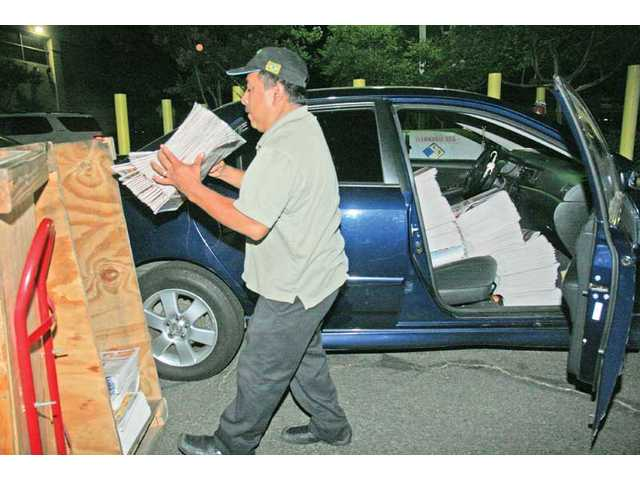 The last stop on the newspaper-production line is delivery. Ranferi Galan fills his car with enough copies of The Signal to fill the 56 newspaper racks on his route.