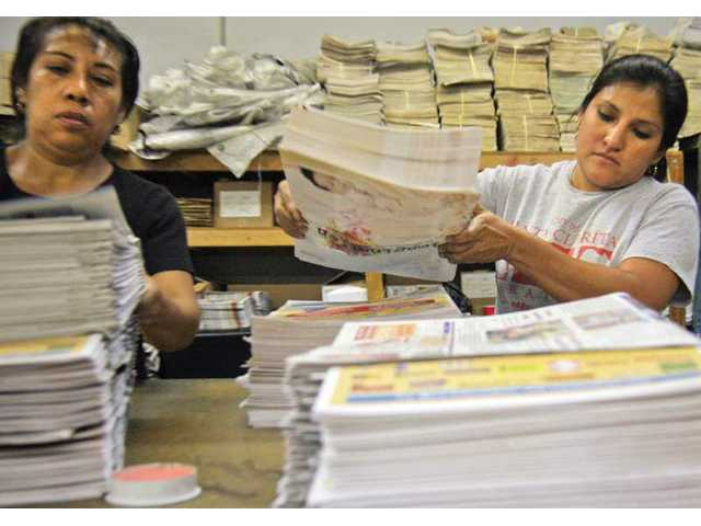 From left to right, Virginia Martinez and Elena Gomez sift and organize about 1,000 inserts into copies of The Signal each Friday morning.