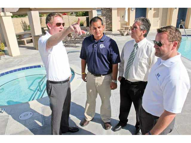 From left to right, Brad Watson, Greg Marquez, Alex Woltman and Kevin Harbison discuss the aesthetics of the pool, spa and landscape during a recent meeting at a community pool in the Plum Canyon.