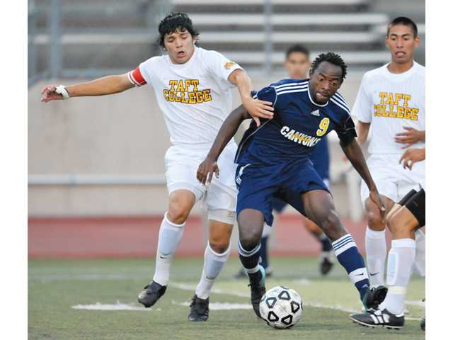 College of the Canyons' Artie Lawson (9) fights for the ball against Taft College's Miguel Guillen (6) in the first half on Tuesday at Cougar Stadium.
