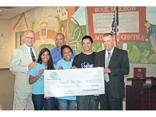 "U.S. Congressman Howard ""Buck"" McKeon, R-Santa Clarita, left, helps present a $25,000 check to the Boys & Girls Club of Santa Clarita Valley. The check was presented by Northrop Grumman with the assistance of students from the Sierra Vista branch of the Boys & Girls Club in Canyon Country, the home of the Howard ""Buck"" McKeon Activities Center."