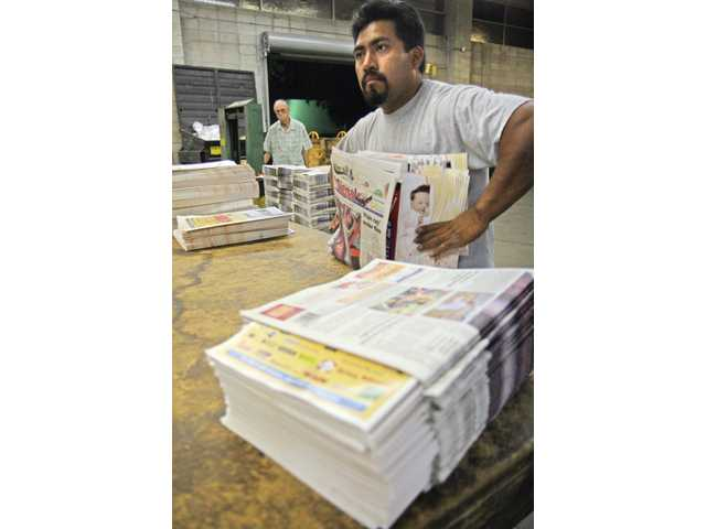 Raul Mendoza stacks newspapers after manually placing inserts into the newspaper at The Signal in Santa Clarita on Aug. 27.