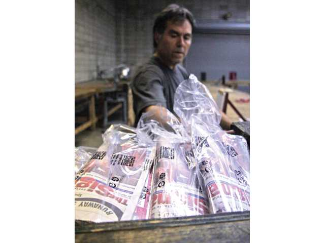 Abel Uballe gathers packaged newspapers to be loaded into his vehicle for delivery on Aug. 27. After packaging anywhere from 500-600 newspapers, Uballe has two delivery routes, which take him four hours to complete.