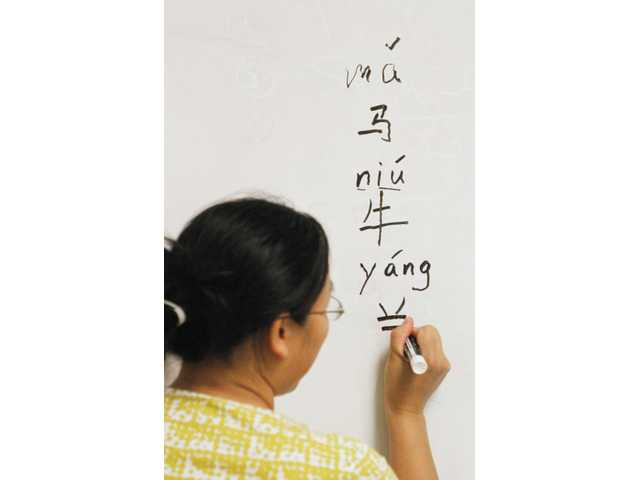 Teacher Jessie Cai writes Chinese phrases on her board during a class session at Santa Clarita Valley Chinese School in Castaic on Sunday.
