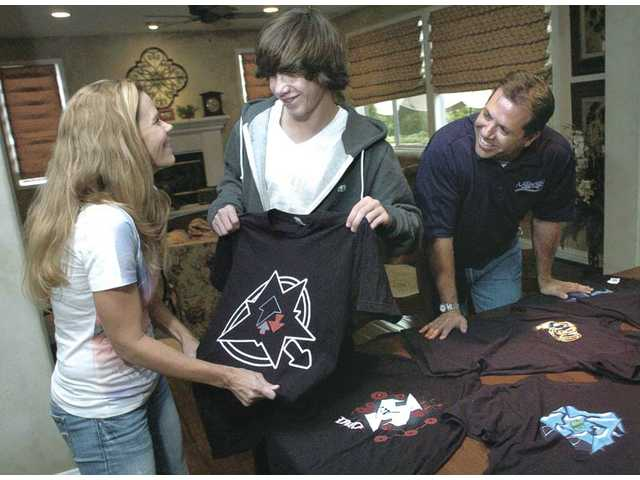 Jake Abramson, 15, center, discusses T-shirt designs with his parents, Debbie, left, and Joshua Abramson. Inspired by Handy's workshop for teens, as well as his father, who's owned his own successful painting business for the last 23 years, Jake is currently working on a marketing and business plan for his company, which produces products targeted to skaters.