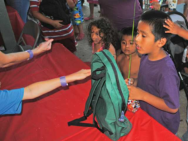 A Val Verde boy moves to the front of the line to accept his free backpack.