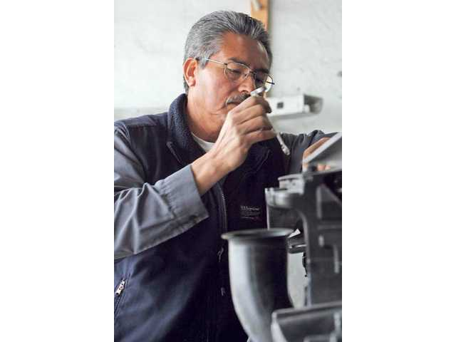 Cuby Cosio works on an engine at Auto Insurance Collision Center in Newhall earlier this year. The location is part of land purchased by the city, a transaction that is forcing the business to relocate.