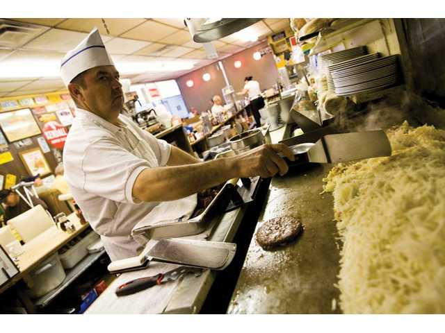 Victor Gonzlaez, who has worked as a cook at Way Station Coffee Shop since 1980, cooks the restaurant's popular hash browns during his shift on an early Tuesday morning.
