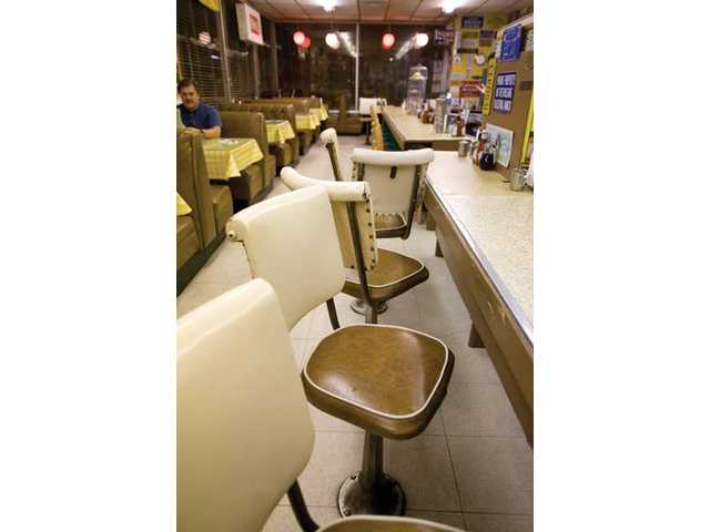 A row of chairs awaits the morning rush of customers at the diner's counter.