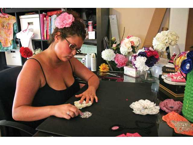 In a recent photo, Ever Fescke makes hair accessories in her Newhall home. Fescke was inspired to make headbands, hair clips and hats after being diagnosed with an immune deficiency disorder that made her lose her own hair.