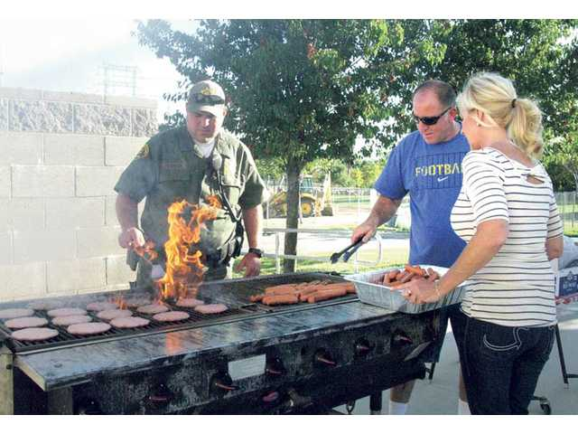 Los Angeles County sheriff's deputies work the grill with the assistance of Kathy Janette, Rosedell's school nurse.