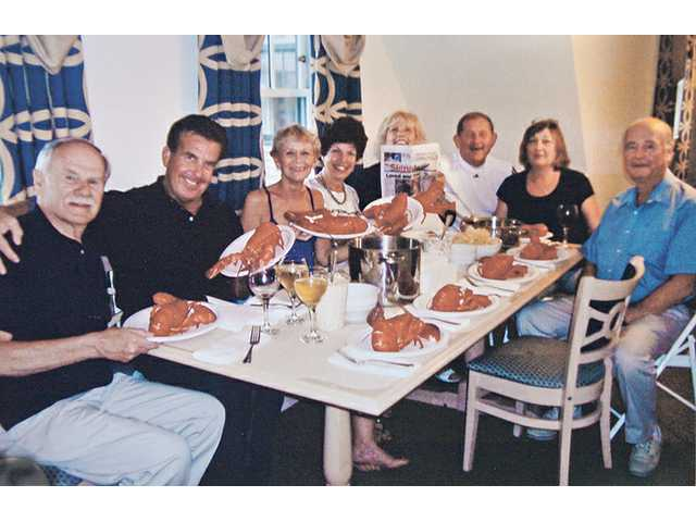 From left, Lee Lodes, Al Hayward, Sue Hayward, Carolyn Lodes, Judy Penman, Jack Skidmore, Dottie Skidmore and Doug Penman enjoy a copy of The Signal and 10 2-pound lobsters as part of Sue Hayward's 60th birthday party in Newport, Rhode Island.