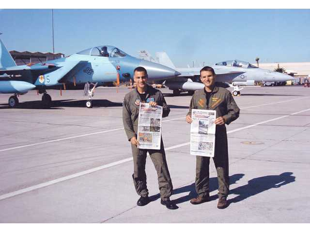 Lt. Col. Paul Johnson of the U.S. Air Force and younger brother Lt. Cmdr. Brian Johnson of the U.S. Navy display their newspapers in front of F-15C and EA-18G fighte jets at Nellis Air Force Base Nevada on Friday. The brothers both grew up in Valencia and graduated from Hart High School in 1987 and 1995, respectively.