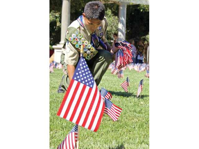 A Santa Clarita Boy Scout plants one of hundreds of tiny American flags used to decorate Veterans Memorial Plaza in Newhall on Saturday in honor of the victims and first responders of the 9/11 terrorist attacks.
