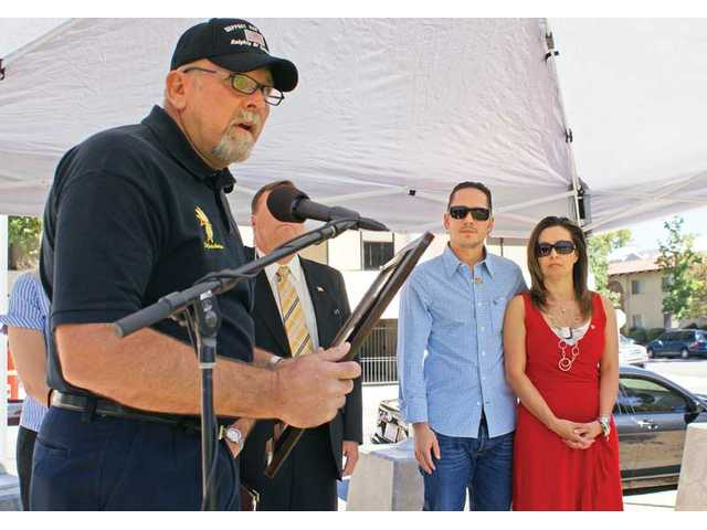 The Santa Clarita Knights of Columbus presents a plaque to fallen United States Marine Corps Pfc. Jake William Suter's stepfather, Chris Unthank, and Suter's mother, Michelle Unthank, at Veterans Memorial Plaza on Saturday during a 9/11 memorial service.