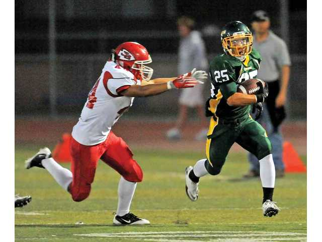 Canyon High senior wide receiver Vinny Rodriguez (25) runs past Burroughs defensive back Frank Aguilar after making a catch on Saturday at Harry Welch Stadium. Canyon won its season opener by the score of 37-31.
