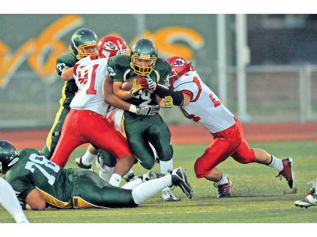 Canyon's Max Archuleta, center, breaks a tackle by Burroughs defenders Nick Brown (91) and Casey Barbello, right, on Saturday at Canyon High School. Canyon won 37-31.