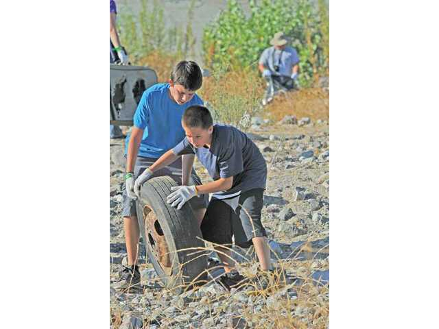 Daniel Leitzell and Wyatt Budge, both 13, get their tire trash over to a dump location in the Santa Clarita River. Volunteers found everything from entertainment units to cars.