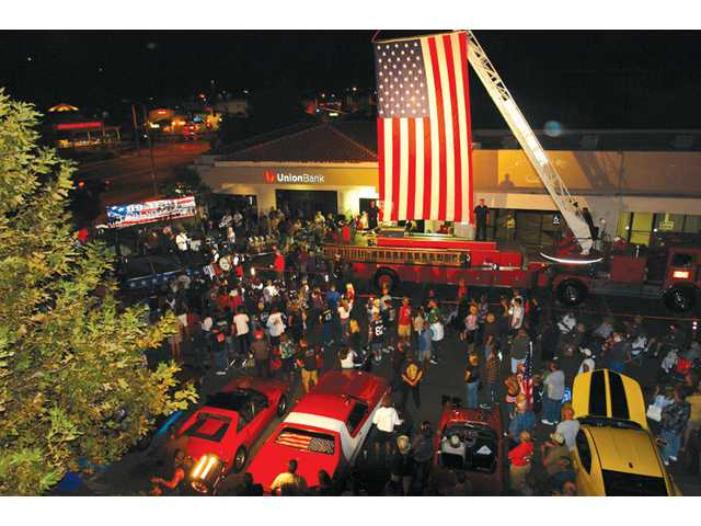A crowd gathers around a large American flag raised by a ladder truck from Los Angeles County Fire Department Station 104  on Saturday at a 9/11 tribute hosted by Route 66 Classic Grill in Canyon Country.