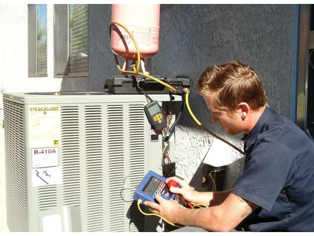 Jeff Frank, a technician for Nicholas Aire Systems, installs an air conditioner at a Saugus residence.