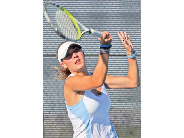 Saugus singles player Jessica Moore returns a serve on Tuesday afternoon at Saugus High School.