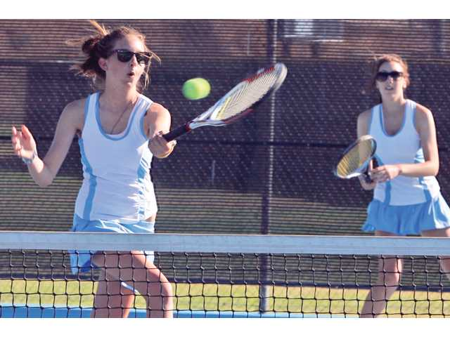 Saugus' No. 1 doubles team member Shelby Johnson, left, returns a serve as partner Amanda Keller watches from the back during a match Tuesday. Saugus won the set 6-2.