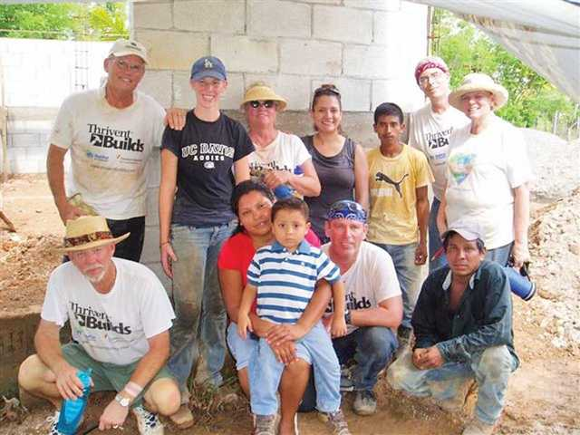 Wayne Schulze, Courtney Hall, Pat Massie, Kevin Liddle, Lynne Putnam and Walt Krego pose with Brenda Robles and her son in front of their new home. The group from Santa Clarita helped build homes in Puerto Barrios, Guatemala for needy families.