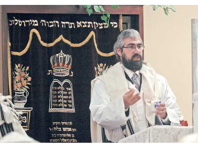 Rabbi Choni Marozov lights a candle before the start of a Yom Kippur service Friday at Chabad of Santa Clarita Valley in Newhall.