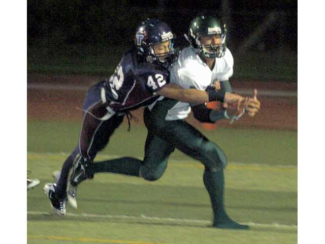 Trinity's Patch Kulp (42) knocks down a pass intended for Ojai Valley's Miles Munding-Becker at Cougar Stadium on Friday.