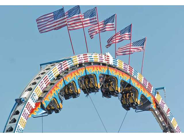 Riders hang upside down on the ride Mega Loop at Our Lady of Perpetual Help's 66th annual fundraiser barbecue on Sunday. The event draws thousands annually and is part of the church's effort to raise $7 million to build a new church.