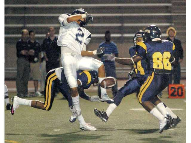 College of the Canyons players Antwan Smith, back left, Travis Briggs (24) and Jarrel Jordan (86) block a punt by Citrus College punter Rauley Zaragoz on Saturday at COC.