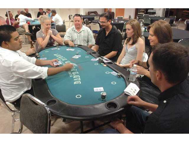 Dealer Kevin Lee, left, tosses cards to a group of Santa Clarita residents at the Shuffle Up and Deal! charity Texas Hold 'em Poker Tournament presented by United Way of Greater Los Angeles and the city of Santa Clarita at the Santa Clarita Sports Complex on Saturday night.