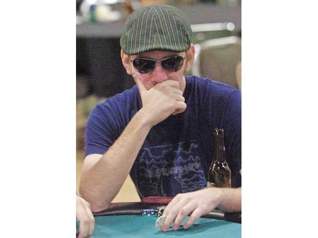 Nathan Imhoff, of Newhall, watches the other players behind sunglasses at the Shuffle Up and Deal! charity Texas Hold 'em Poker Tournament  presented by United Way of Greater Los Angeles and the city of Santa Clarita at the Santa Clarita Sports Complex on Saturday night.