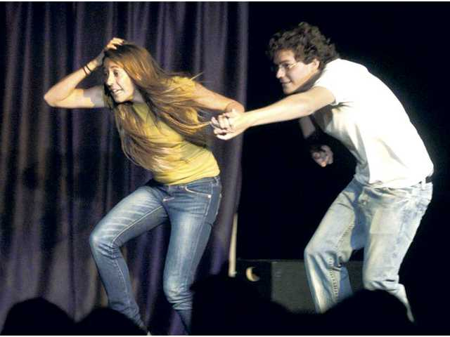 "Saugus High School students Kaylin Mahoney, left, and Joe Veliz run from a shark as they improvise a scene in an improv game called switch genre at the ""We Got Scissors"" improv show held before a packed house in the Saugus High School multipurpose theater room on Thursday night."