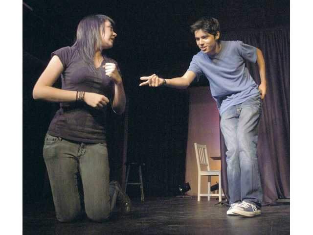 "Saugus High students Becky Allen, left, and Avery Rodriguez play a bank robber and cop who fall in love during a robbery as two students off stage dub their actions at the ""We Got Scissors"" improv show."