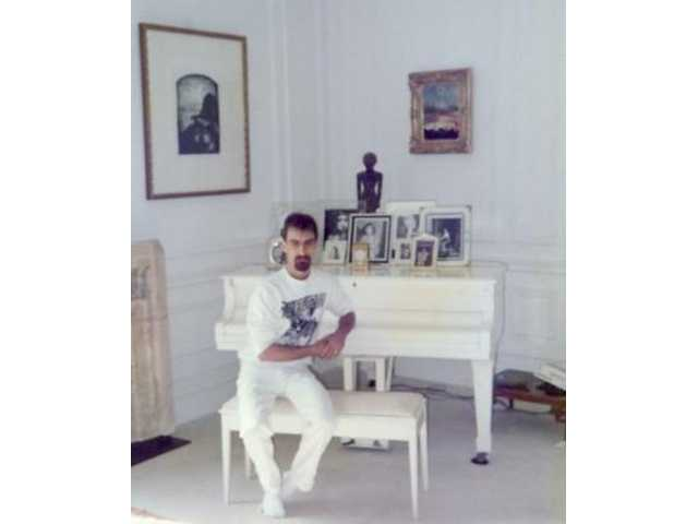 "In this July 1989 photo, the author sits at the white piano on which John Lennon wrote ""Imagine"" and other classics. It still resides in the White Room at the Dakota apartments in New York."