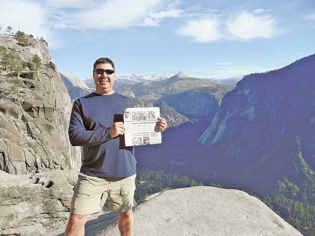 Brett Rateaver holds up a copy of The Signal at the top of Upper Yosemite Falls in Yosemite Park on Oct. 26.