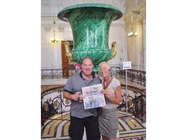 Richard Candib and Linda Candib hold up a copy of of the newspaper in front of a large malachite vase at the top of the Council Staircase of the State Hermitage museum in St. Petersburg, Russia on July 12 as part of 10-day cruise in the Baltic Sea.