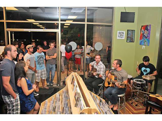 Local band Fentruck, right, performs for a couple hundred music fans at the grand opening of Rock Candy Music and More in Saugus on Saturday. The McGrath Project also performed.