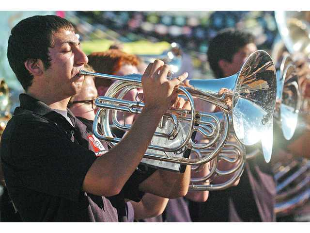"Thomas Jentis, 17, of the Hart High marching band, performs ""Just Dance"" on the French horn at the Our Lady of Perpetual Help annual barbecue fair in Newhall on Saturday"