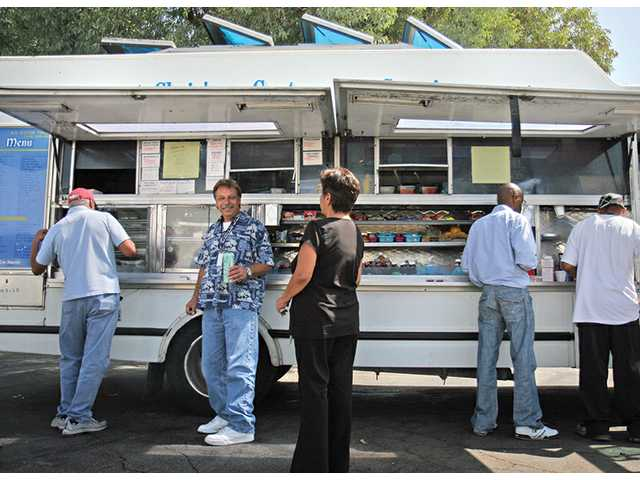 Employees of Wesco Aircraft wait around a Santa Clarita Catering food truck during their lunch break on Tuesday afternoon. Los Angeles County officials want to pass an ordinace that would require all trucks to post letter grades on their windows.