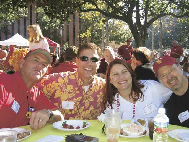 Whether it's a classy group gathering at USC or a parking lot celebration, football season is also the season for tailgating. These USC fans are, left to right, Burt Umstead, John Dow, Michelle Dow and Jim Blazer.