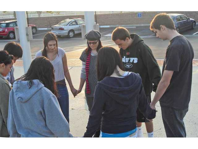 A group of Valencia High students holds hands and prays for its school and the nation on Wednesday. The group continued to grow as the beginning of the school day drew closer. Just before the second period bell rang, about a dozen Christian students had gathered in prayer.