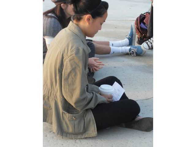 Allison Harada, president of Pathfinders Christian Club at Valencia High, bows her head in prayer. She prayed for those with financial difficulties and for the group to have courage in their faith while on campus.