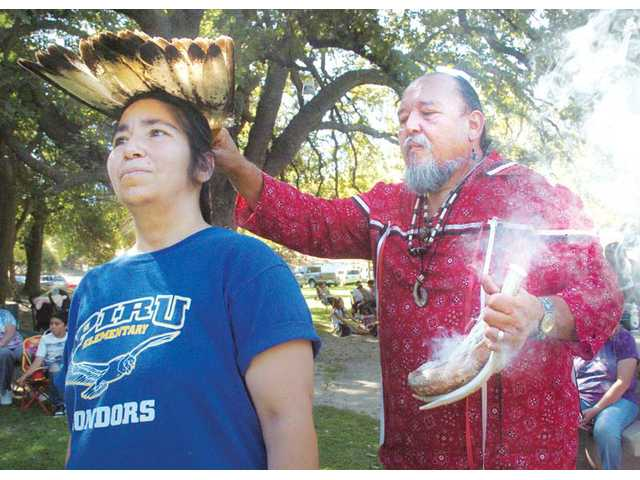 Ted Garcia, right, performs a sage purification ritual and blessing on Tillie Quijada, of Piru, at the Pow Wow.