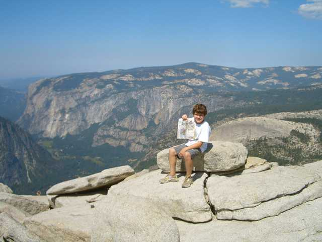 Eric Ortiz sits on top of Half Dome in Yosemite during a recent trip with father, Chris Ortiz.