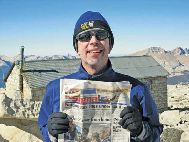 Tony Dulgeroff, of Valencia, holds a copy of The Signal on the summit of Mount Whitney. Mount Whitney is the highest summit in the contiguous United States, with an elevation of 14,505 feet.