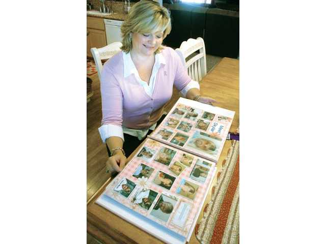Galbreath looks over her breast cancer scrapbook, which includes photos of friends and family wearing her blonde wig.
