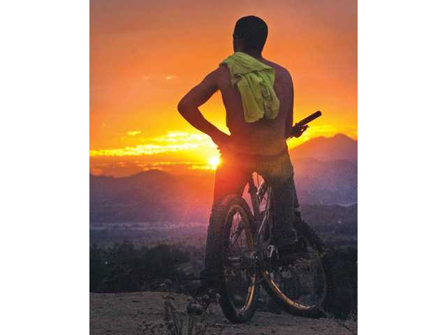 Curt Philips, 19, watches the sunset Thursday from the seat of his mountain bike at the end of Catala Avenue near Garza Drive in Saugus.